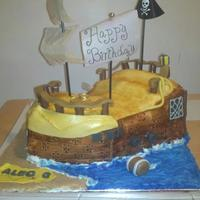 Pirate Ship Cake Boys Birthday This is a yellow cake covered in fondant on a cake board with royal icing water and waves and brown sugar sand