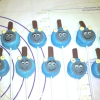 Thomas The Train Cake Pops Chocolate cake pops shaped into cylinders, fondant face, candy necklace pieces for headlights and half a tootsie roll for the steam pipe