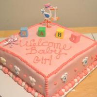 "Pink Baby Shower Cake Girl Stork Pink baby shower cake covered in fondant and includes sugar ""onesies"", blocks, rattles and stork"