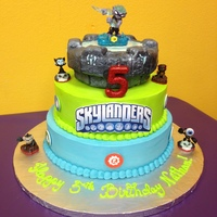 Skylander Cake With A Chocolate Bottom Tier White Middle And Rct Top Covered In Fondant Characters Were Purchased And The Logo Was Done O Skylander cake with a chocolate bottom tier, white middle and RCT top covered in fondant. Characters were purchased and the logo was done...