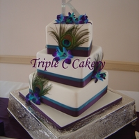 Pretty Peacock 3 tiered offset square cake with accents of peacock feathers and orchids.