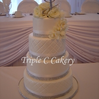 White On White And Blingy! 4 tiered cake with diamante borders and quilting.