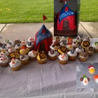Circus Tent Tent covered w/MMF cupcakes are topped with royal icing clowns and animal heads and tails.
