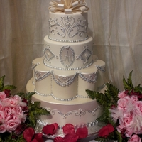 Wedding Covered in marshmallow fondant. Piping in royal icing, gumpaste bow,luster dust painting