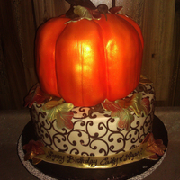 "Autumn Birthday Cake 3d pumpkin cake on top of a chocolate scroll covered tier. Pumpkin is 3 8"" round layers, carved, and covered in MFF. Bottom tier is 10..."