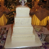 Square Wedding Cake Buttercream icing with hand piped swirls. Pearls were made out of fondant.