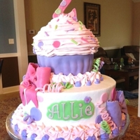 Cupcake Cake This is a 10inch buttercream iced cake with a giant cupcake on top. Decorations are fondant. Cupcake liner is also made with fondant.