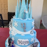 Frozen Themed Cake And Cupcakes. Frozen themed cake with stairs, snowflakes and a hand made castle on top.