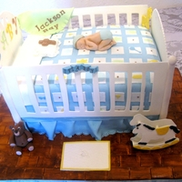 Baby Crib Vanilla cake with strawberry filling. Iced in SMB and fondant. Crib rails, bear, rocking horse, and floor mat are gumpaste. Baby was made...