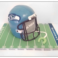 Seahawks Seahawks helmet for my son's birthday. Vanilla cake with caramel smbc filling. Iced in smbc and fondant. Edible image. The face grill...