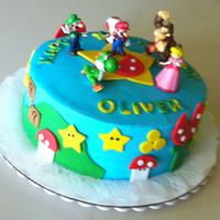 "Mario 9"" round, buttercream with fondant decorations. Figures on top are the birthday boy's special toys!"
