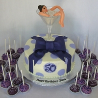 "Purple Present Cake this is a 9"" red velvet cake with cream cheese frosting, fondant decor, various shades of purple with some cake pops. fondant figure..."