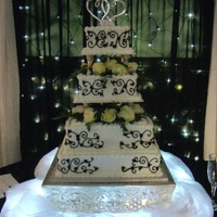 Black & White 4 tier , iced in buttercream with black scroll designs.
