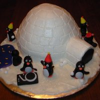 Penguin Party Igloo made from doll pan + 1 cupcake and covered in BC. Poured BC blue pond and white ground cover. Penguins are fondant. Edible glitter...