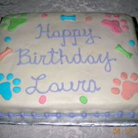 Paw Print Cake White 11X15 single layer cake. White BC icing with fondant accent paws and bones. Colors were matched to coordinating tablecloth for girl&#...