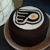 "Rich Chocolate Groom's Cake A Philadelphia Flyer's ""puck"". Chocolate cake and filling, black fondant, and a gum paste/fondant disc on top."
