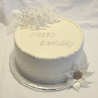 "Winter White Birthday Iced in buttercream. Gumpaste poinsettia, snowflakes and ""happy birthday"" are chocolate"