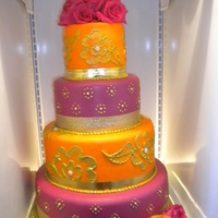 Indian Wedding Cake you cant tell from the lighting but the fushia color matched the roses.....very gold scroll work