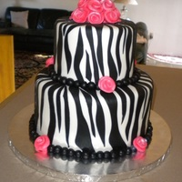 Zebra Print Cake 9 and 6 zebra print cake covered in mmf with hand rolled luster dusted hot pink flowers and fondant ball border. Dark chocolate cake with...