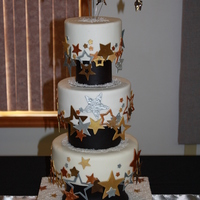Michelle 3 tier fondant wedding cake with black column separators and hanging star topper. Stars are gumpaste airbrushed in metallic colors.
