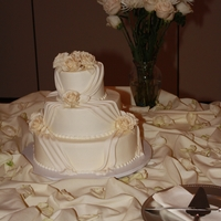 Ivory Wedding With Drapes And Roses 3 tier round cake iced in cream cheese frosting with fondant draping and ivory gumpaste roses.