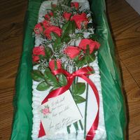 Roses Are Red Single 13X9 cake split long. Florist tape wrapped around plastic stems.Poster board box with green florist paper. Cake is topped with hand...