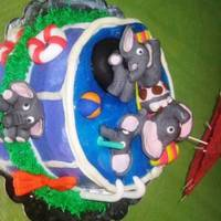 Elephants At The Pool  This is a spice cake with cream cheese frosting. Blue gel icing for the water. Everything else is fondant except for the cocktail umbrella...