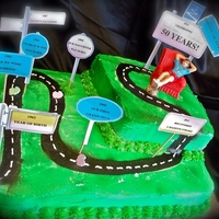 Milestone Cake Two tiered cake of Almond Cream & Chocolate. Airbrushed w/cutout milestone road signs