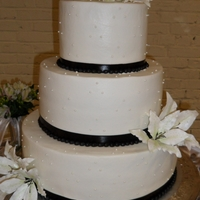 Lilies And Pearls  Iced in buttercream, this round wedding cake was trimmed out with black ribbon and gum paste Oriental Lilies colored to match the black...