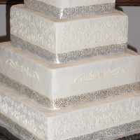Mallory's Wedding Cake Iced in bc with bc piping. Edible pearls are dusted in silver and gold luster dust. Each tier is wrapped with cream and gold ribbon.