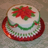 Poinsettia An 8x4 round iced in b'cream. The poinsettia is created from fruit leather. Holly leaves are fondant. Swags are piped from tip 233 in...