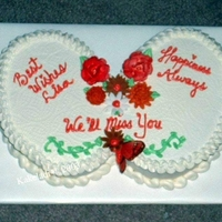 1322949292.jpg Two small oval cakes are placed side-by-side on a 1/2 sheet board covered with freezer paper. This is an all b'cream cake, including...