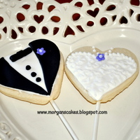 Bride And Groom Cookie Pops These bride and groom cookies are decorated with fondant and buttercream. They are on a stick to be toppers on a wedding cake.