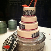 Brimms And Stiletoos Stunning four (4) tier cake with stiletto and fedora houndstooth pattern hate. Cake flavors - marble, chocolate and yellow. Fedora hat made...