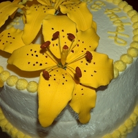 Yellow Oriental Lilies Chocolate cake filled and frosted in whip cream. Lilies are fondant. First time making them, a few improvements for next time.