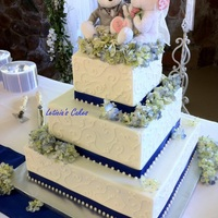 Bears And Blue   Buttercream with satin ribbon. Hydrangeas have wax paper under them so they won't touch the icing.
