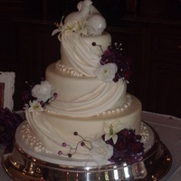Pearls And Drapes MMF covered white cake with raspberry filling.