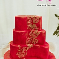 Henna Design Fondant covered then airbrushed red with gold luster dust. Piped royal icing design then hand-painted with gold luster dust