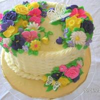 Wilton Course 3 Final Cake Yellow buttercream icing basketweave around sides of oval cake. A variety of flowers from the Wilton Course 3 program. Violets, Daffodils,...