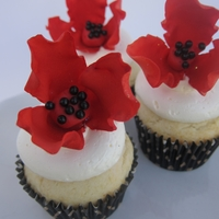 Graduation Cupcakes Red and black were the graduate's school colors. Flower is gumpaste sitting on SMBC and vanilla cupcake.