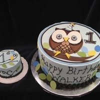 Owl Cake With Smash Cake Owl cake done for a one year old boy. Done to match the invitation and party supplies. Buttercream outside with fondant accents.