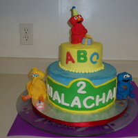 Sesame Street Birthday Cake Cake is WASC with a layer of cheescake as the filling. It is covered in vanilla buttercream with fondant accents. Figures made of rice...