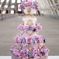 Marie Antoinette Wedding Cake A purple ombre Marie Antoinette wedding cake decorated with large roses, gold cherubs and gold swags.