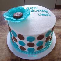 Flower And Dots 8 inch white cake frosted with buttercream and decorated with teal and brown marshmallow fondant dots/circles and a large flower. This was...