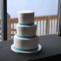 White And Teal With Burst fondant covered with burst imprint and gumpaste callas. teal fondant ribbon border