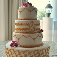 Elegant Gold And White Fondant covered cake with gold royal icing piping, sugar flowers.