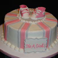 Baby Shower High Top Baby Shoes Dark Chocolate cake with Raspberry BC filling. Plaque and high tops are from gum paste