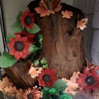 Tree Stump Cake Display cake. Covered in royal icing. Hand made gumpaste flowers and black berries. Butterflies also made out of gumpaste.