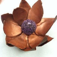 Chocolate Flower Flower made out of choclate. Chocolate center covered in purple sugar. Bronze color used to dust petals.