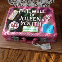 "Farewell To Youth Suitcase cake with Camo background trimmed in pink and silver. ""Travel stickers"" with ""old age"" sayings."